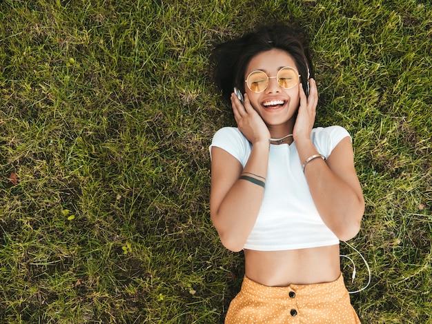 Mode portrait de jeune femme hipster élégant allongé sur l'herbe dans le parc. fille à la mode tenue à la mode. modèle souriant profiter de ses week-ends. femme, écoute, musique, écouteurs, haut, vue