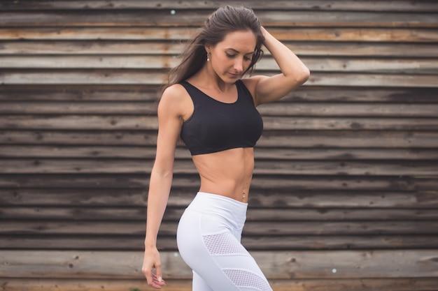 Mode portrait d'une jeune fille athlétique en forme de vêtements de sport en plein air. femme avec un corps parfait concept de remise en forme.
