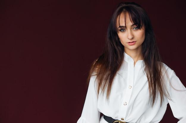 Mode portrait de jeune fille dans une élégante robe blanche avec une ceinture noire. portrait. beau maquillage.