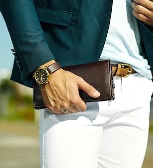 Mode portrait de jeune homme d'affaires beau modèle homme en costume de tissu décontracté avec accessoires sur les mains