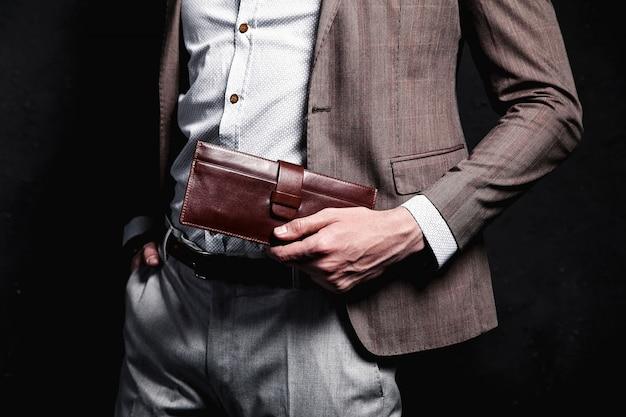 Mode portrait de jeune homme d'affaires beau modèle homme habillé en élégant costume marron avec accessoires