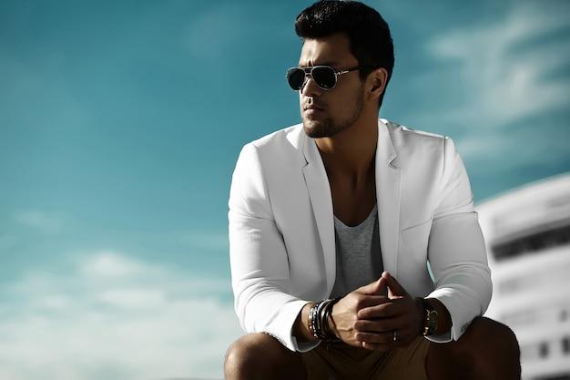 Mode portrait de jeune homme d'affaires sexy beau modèle homme en costume de tissu décontracté à lunettes de soleil assis dans la rue derrière le ciel bleu