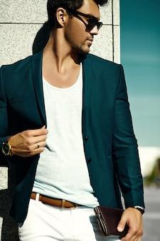 Mode portrait de jeune homme d'affaires sexy beau modèle homme en costume de tissu décontracté à lunettes de soleil dans la rue