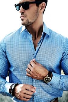 Mode portrait de jeune homme beau modèle sexy en tissu décontracté à lunettes de soleil dans la rue