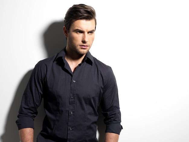 Mode portrait de jeune homme en chemise noire pose sur le mur avec des ombres de contraste