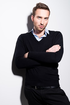 Mode portrait de jeune homme en pull noir et chemise bleue avec les bras croisés