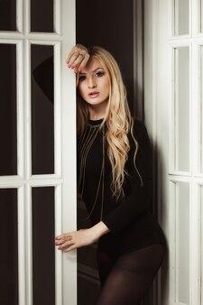Mode portrait d'une jolie femme blonde en sous-vêtements noirs et bas