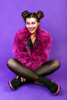 Mode portrait de jolie femme, maquillage lumineux, coiffure de fête folle, manteau en fausse fourrure à la mode. assis par terre et souriant et riant, joie, positif.