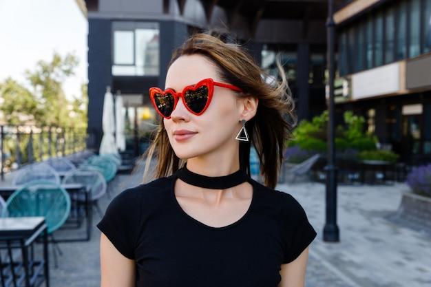 Mode portrait de jolie femme en t-shirt noir et jupe rouge marchant dans la rue