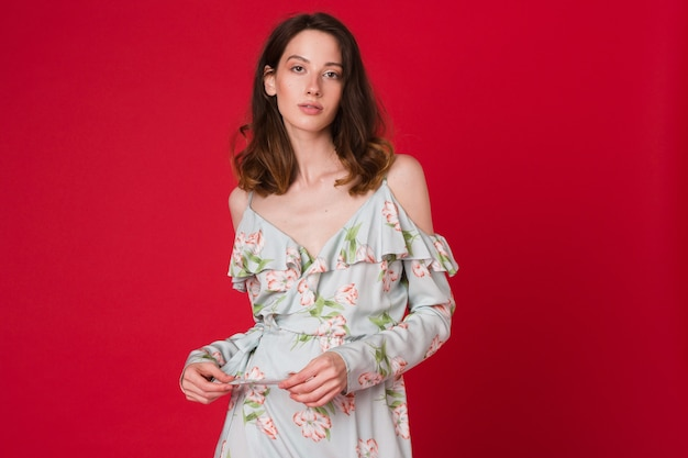 Mode portrait de jolie jeune femme en robe imprimée bleue sur studio rouge