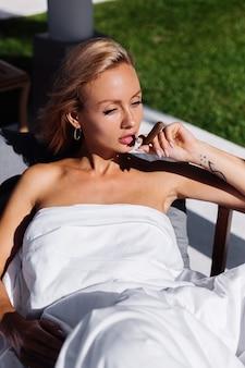 Mode portrait en plein air de femme nue est assise sur un canapé se couvrant avec une couverture tenant un cigare