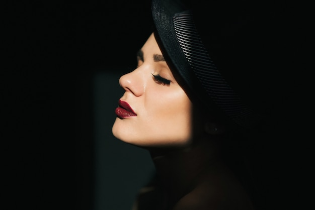 Mode portrait de profil d'une jeune fille sexy avec un chapeau noir avec rouge à lèvres