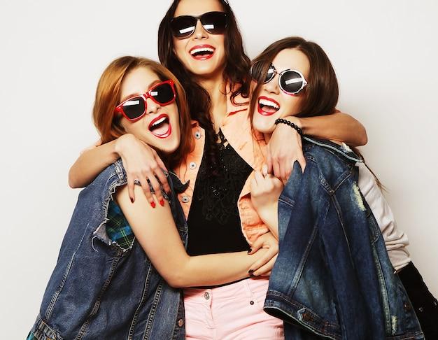 Mode portrait de trois meilleures amies élégantes de filles hipster sexy, sur fond gris. bon moment pour s'amuser.