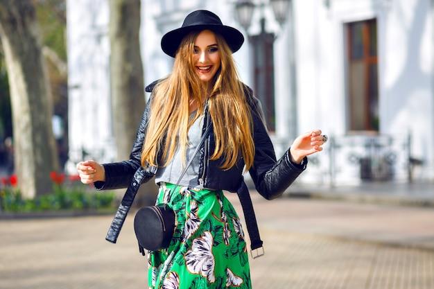 Mode portrait de ville en plein air de femme hipster élégante marchant dans la rue et s'amusant, femme jeune voyageur, fashionista, tenue de beauté féminine, jupe longue vintage, chapeau rétro et veste de motard.