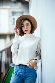 La mode de la rue intéressée femme portant un chapeau, un jean bleu, un chapeau large et des lunettes transparentes sur balcon