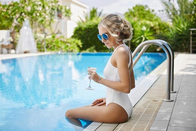 À la mode et sexy jeune mannequin femme blonde en maillot de bain, avec un verre de champagne dans les mains, posant à la piscine en plein air
