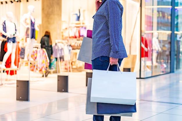 Mode shopping girl portrait. beauté femme avec des sacs à provisions au centre commercial. client. ventes.