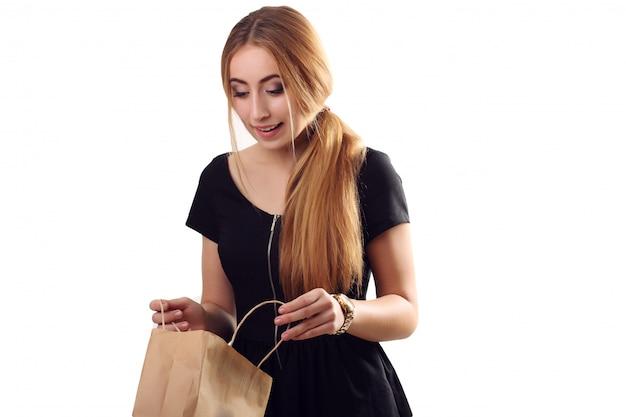 Mode shopping girl portrait. regarder dans le sac ravi beauté femme avec sac à provisions au centre commercial. client. ventes. centre commercial