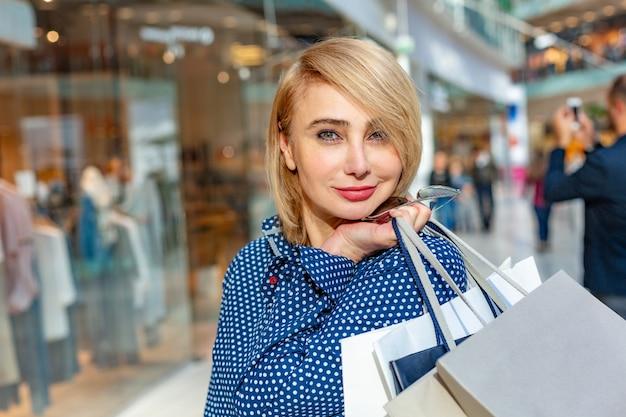 Mode shopping portrait de jeune fille. beauté femme avec des sacs de shopping au centre commercial. client. ventes.