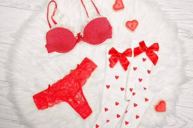 Mode . soutien-gorge rouge et culotte string, bas blancs avec des arcs, des bougies en forme de coeur sur une fourrure blanche. vue de dessus