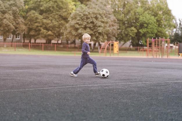 Mode de vie actif dans une ville moderne - petit garçon jouant avec un ballon de football au stade