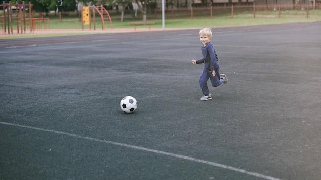 Mode de vie actif dans une ville moderne - petit garçon jouant avec un ballon de football dans le stade