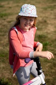 Mode de vie actif des enfants modernes - belle fille blonde se promène avec un vélo sur le terrain
