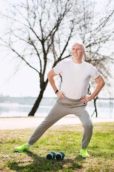 Mode de vie actif. homme mûr attrayant travaillant dans le parc et souriant