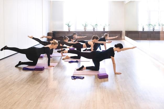 Mode de vie actif et sain, passe-temps, loisirs, bien-être, concepts de perte de poids. groupe de filles danseuses s'échauffant avec des exercices d'étirement pour plus de flexibilité pendant les cours dans une salle de sport blanche