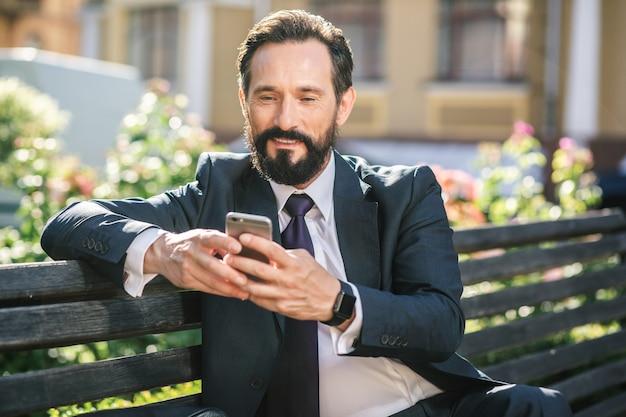 Mode de vie des affaires. taille d'un homme souriant positif assis sur le banc tout en utilisant son smartphone