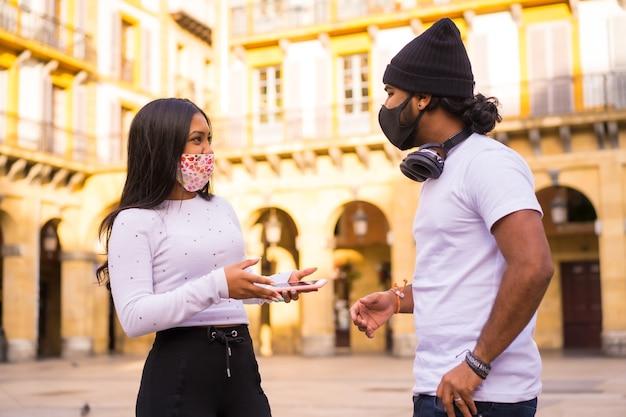 Mode de vie, amis parlant lors d'une réunion avec des masques faciaux.