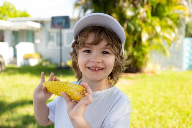Mode de vie d'automne aliments biologiques cultivés sur place végétalien enfants nutrition garçon heureux mangeant du maïs en épi