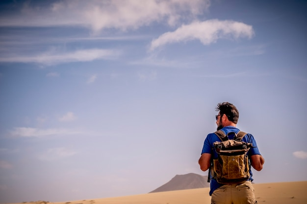Mode de vie aventure avec homme explorateur avec sac à dos vu de dos marchant seul dans le désert et les montagnes