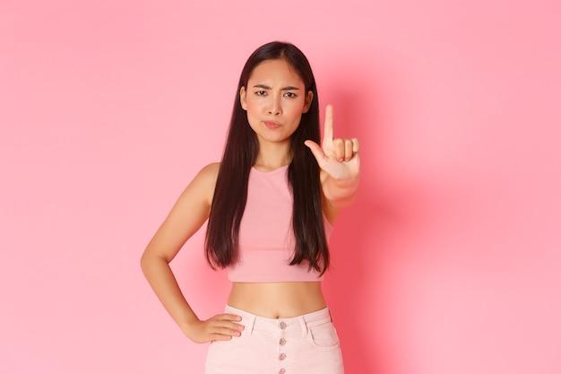 Mode de vie beauté et femmes concept portrait d'une fille asiatique sérieuse et mécontente essayant d'avertir p...