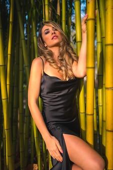 Mode de vie blonde fille de race blanche dans une robe noire glamour dans le parc dans la nature perchée sur de beaux bambous à la mode perché sur des bambous