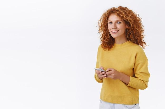 Mode de vie, concept technologique. jolie fille rousse aux cheveux bouclés avec pull jaune, tenir un smartphone, caméra souriante joyeusement, attendant un taxi, commander de la nourriture via l'application de livraison, mur blanc