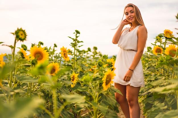 Mode de vie dans la ville de pampelune, une jeune blonde en robe blanche à la recherche dans un champ de tournesols