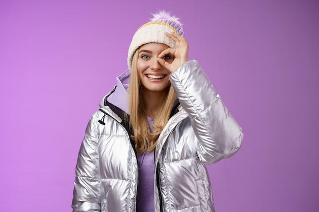 Mode de vie. élégante étudiante européenne insouciante profitant d'un voyage de vacances dans un pays enneigé portant une veste en argent à la mode chaude, un chapeau tricoté, un bon geste, un geste génial souriant s'amuser, recommander la station.
