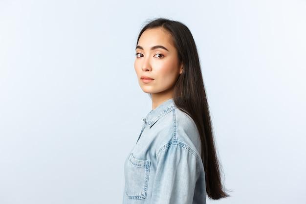 Mode de vie, émotions des gens et concept de beauté. belle femme asiatique rêveuse aux cheveux longs noirs, debout de profil et se tourner vers la caméra avec une expression sérieuse et réfléchie