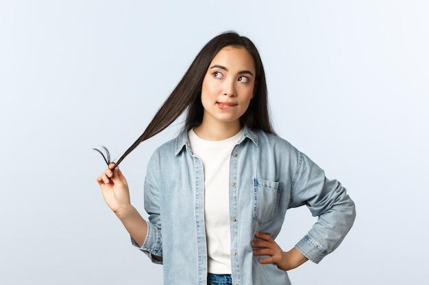 Mode de vie, émotions des gens et concept de beauté. une fille asiatique sérieuse et sérieuse qui roule une mèche de cheveux tout en pensant, en détournant les yeux, en réfléchissant à la décision, sur fond blanc.