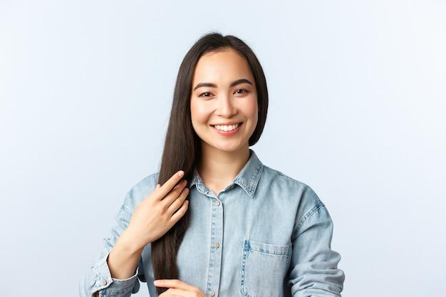 Mode de vie, émotions des gens et concept de beauté. jolie fille asiatique rêveuse souriante et touchant de longs cheveux noirs raides, essayant de nouveaux produits capillaires, visitez un coiffeur ou un salon de beauté