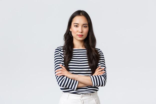 Mode de vie, émotions des gens et concept décontracté. confiant, belle femme asiatique souriante, bras croisés sur la poitrine, confiante, prête à aider, à l'écoute de ses collègues, prenant part à la conversation