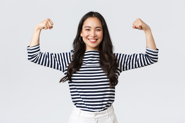 Mode de vie, émotions des gens et concept décontracté. une femme asiatique forte et confiante fléchit les biceps, se vantant de sa forme parfaite après s'être inscrite à la salle de sport, se vanter de ses muscles, s'entraîner et se sentir forte