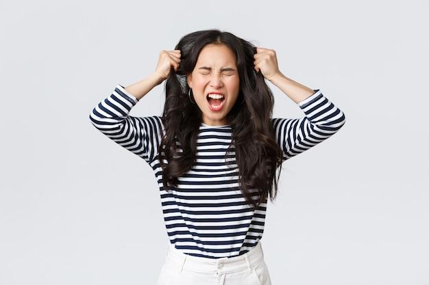 Mode de vie, émotions des gens et concept décontracté. jeune femme asiatique folle et en colère énervée jetant les cheveux, les tirant de la tête avec des cris et les yeux fermés, debout sur fond blanc dérangé