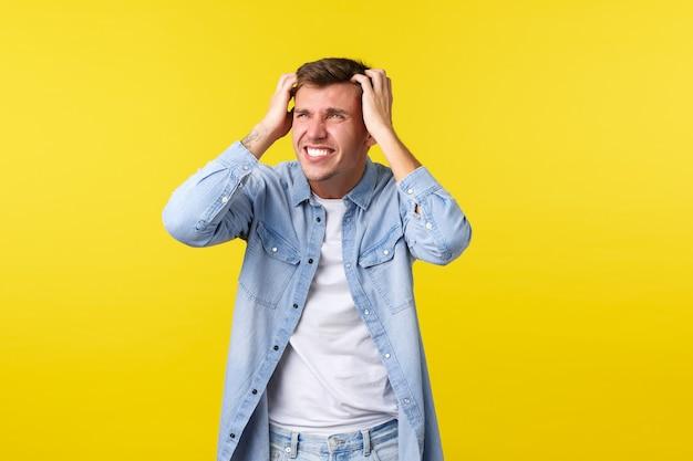 Mode de vie, émotions des gens et concept de loisirs d'été. un homme blond inquiet et anxieux attrape la tête et a l'air désespéré, joue, regarde l'échec, perd et est en détresse, regarde à gauche.