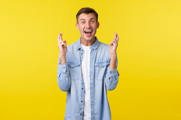 Mode de vie, émotions des gens et concept de loisirs d'été. un homme blond rêveur plein d'espoir croise les doigts et sourit excité, prie ou supplie, anticipe la délectation, croit sur fond jaune.