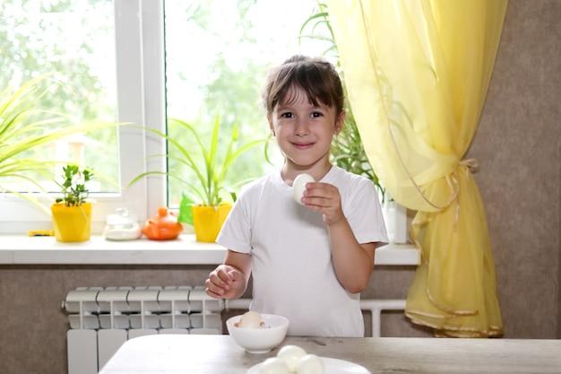 Mode de vie enfant d'âge préscolaire fille cuisiner des aliments dans la cuisine. développement de la motricité fine dans la vie quotidienne à partir de matériaux de récupération. l'enfant nettoie les œufs.