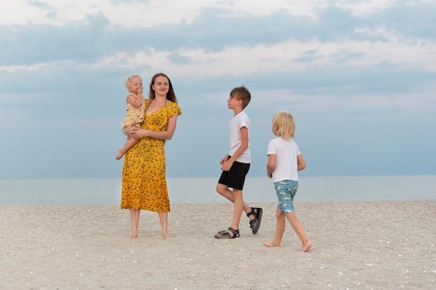 Mode de vie familial. maman et trois enfants marchent le long de la plage de sable sur fond de mer.