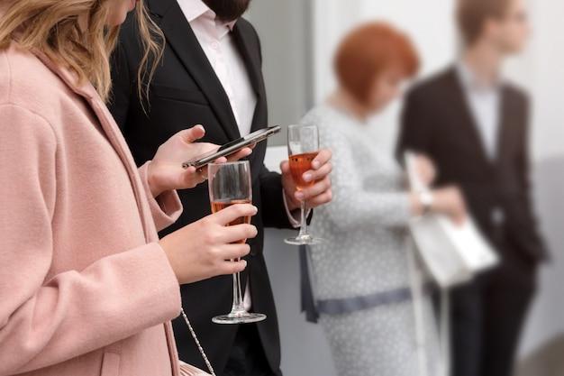 Mode de vie de fête moderne - un groupe de jeunes tenant des verres de vin mousseux et utilisant des smartphones.