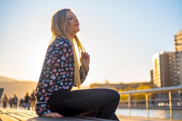 Mode de vie, fille blonde profitant de la ville avec une chemise bleue et un pantalon noir